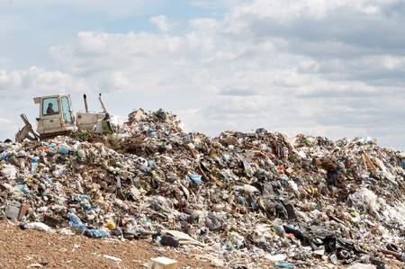 Bulldozer working on mountain of garbage in landfill photo
