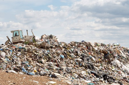 utilize: Bulldozer working on mountain of garbage in landfill
