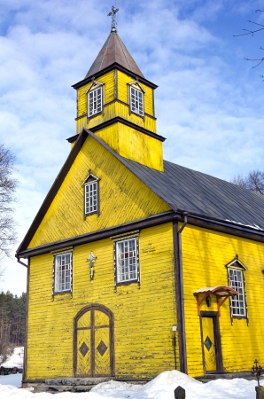 vilnius:  Folk architecture forms, wooden yellow Silenai Church of the Virgin Mary stands Silenai village, 16 km west of Vilnius
