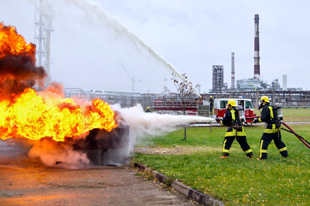 Two firefighters in protective uniform and helmet extinguish a fire with foam against the background of the oil refinery.Firefighter training. Editorial