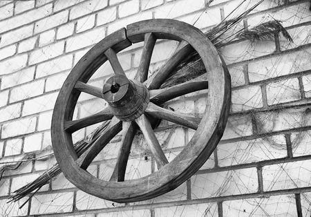 carreta madera: Antique madera colgante rueda de carro en una pared de ladrillo como decoración.