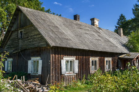 Old, rustic, abandoned wooden house with white windows and eternit roofed with smoking chimneys Stock Photo