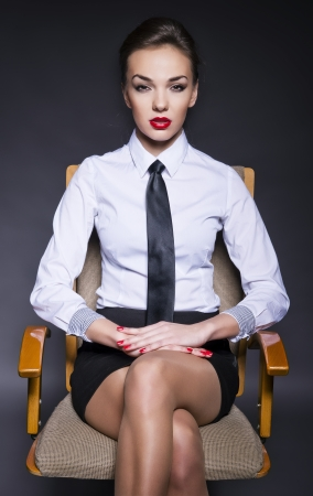neckties: attractive businesswoman sitting on the chair Stock Photo