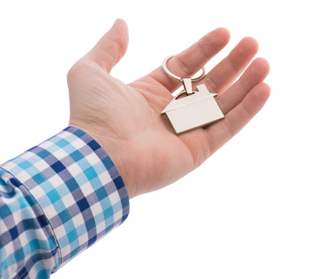 Close-up Of Hand giving a key ring with house isolated on white  photo