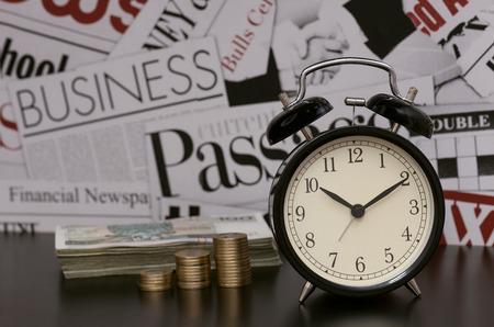 financial metaphor: El tiempo es dinero, negocios, met�fora financiera, reloj, monedas, en el escritorio Foto de archivo