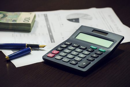 financial planner: Business office desk with pen calculator charts and money