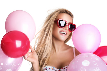 Young beautiful woman with glasses holding pink balloons, valentines day, isolated