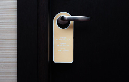 hotel door: Do not disturb sign handle on a hotel door close up