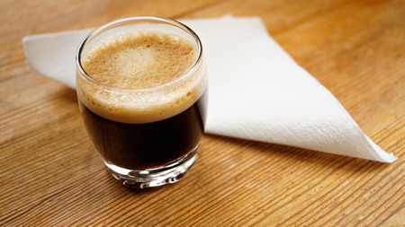 A small glass of coffee with a napkin paper Stock Photo