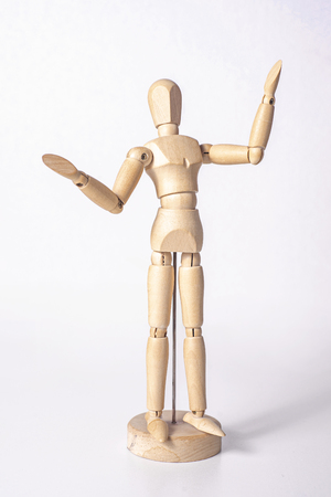 A wooden mannequin is happy jumping up and raising one hand up, isolated on white background