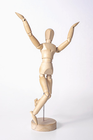A wooden mannequin is happy jumping up and raising its hands up, isolated on white background