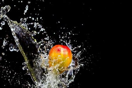 Mango splashing over clear water on black background photo