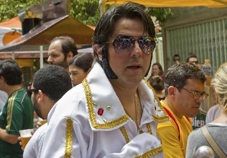 elvis presley: SAO PAULO, BRAZIL - JANUARY 31, 2015: An unidentified man dressed like Elvis Presley participate in the annual Brazilian street carnival dancing and singing samba.