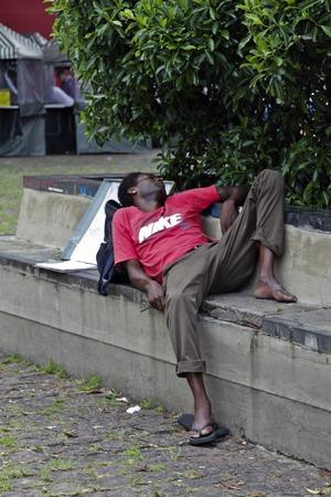 SAO PAULO, BRAZIL - FEBRUARY 08, 2015: An unidentified homeless sleeping in front of the famous Paulista Avenue in São Paulo Brazil.