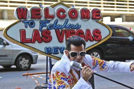 elvis presley: SAO PAULO, BRAZIL - FEBRUARY 08, 2015: An unidentified street musician imitates Elvis Presley dressed with typical vintage rock dress in Paulista Avenue at Sao Paulo Brazil. Editorial