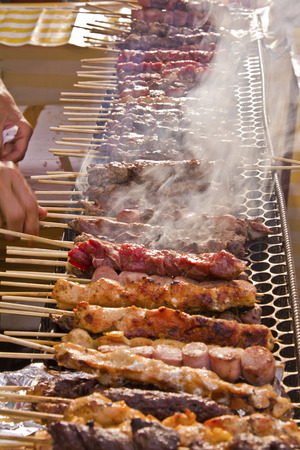 to tend: Street fair tend of skewered meat with smoke Stock Photo