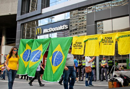 federal government: SAO PAULO, BRAZIL August 16, 2015: An unidentified woman walks in front of a flag vendor in the protest against federal government corruption in Sao Paulo Brazil. Protesters call for the impeachment of President Dilma Rousseff. Editorial