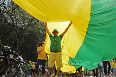 federal government: SAO PAULO, BRAZIL August 16 2015: An unidentified man below of a big flag in the protest against federal government corruption in Sao Paulo Brazil. Protesters call for the impeachment of President Dilma Rousseff.