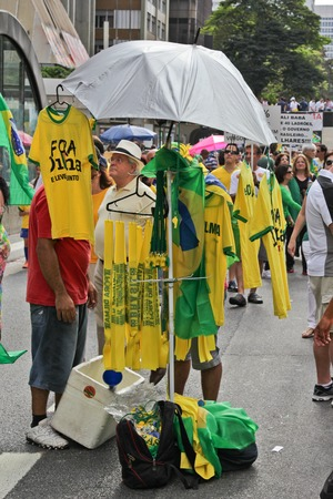 protesters: SAO PAULO, BRAZIL August 16, 2015: Flags and T-Shirts to sell in the protest against federal government corruption in Sao Paulo Brazil. Protesters call for the impeachment of President Dilma Rousseff.