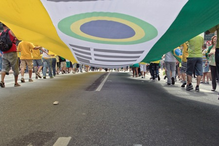 federal government: SAO PAULO, BRAZIL August 16, 2015: An unidentified group of people hold a big flag in the protest against federal government corruption in Sao Paulo Brazil. Protesters call for the impeachment of President Dilma Rousseff.