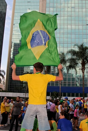 federal government: SAO PAULO, BRAZIL August 16, 2015: An unidentified man with a flag in the protest against federal government corruption in Sao Paulo Brazil.