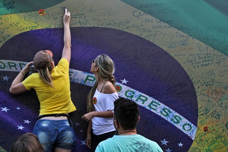 demonstration: SAO PAULO, BRAZIL August 16, 2015: Two unidentified women  signing a large brazilian flag in the protest against federal government corruption in Sao Paulo Brazil.