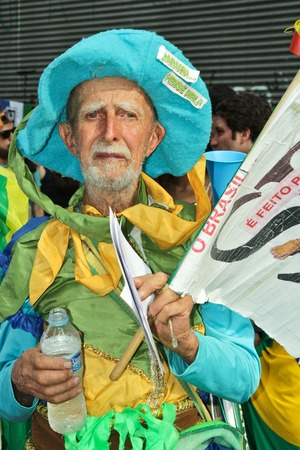 federal government: SAO PAULO, BRAZIL August 16, 2015: An unidentified man with yellow green and blue costume in the protest against federal government corruption in Sao Paulo Brazil. Protesters call for the impeachment of President Dilma Rousseff.