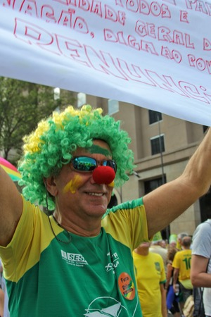 protesters: SAO PAULO, BRAZIL August 16, 2015: An unidentified man with yellow and green clown costume in the protest against federal government corruption in Sao Paulo Brazil. Protesters call for the impeachment of President Dilma Rousseff.