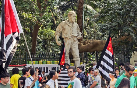 silva: SAO PAULO, BRAZIL August 16, 2015: An unidentified group of people with flags in front of Bartolomeu Bueno da Silva statue in  the protest against federal government corruption in Sao Paulo Brazil. Editorial