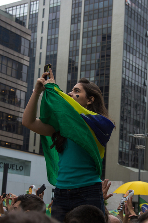 federal government: Sao Paulo Brazil March 13, 2016: One unidentified girl taking a selfie in the biggest protest against federal government corruption in Sao Paulo.