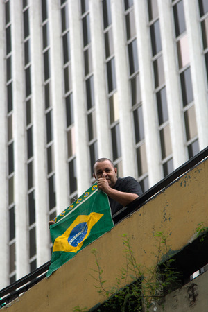 federal government: Paulo Brazil March 13, 2016: One unidentified man with brazilian flag in the biggest protest against federal government corruption in Sao Paulo.