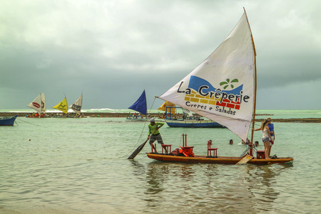 northeast: Pernambuco, Brazil July 6, 2016: An unidentified group of people in Chicken Beach with typical sail boats in Ipojuca City near barrier reef, northeast Brazil
