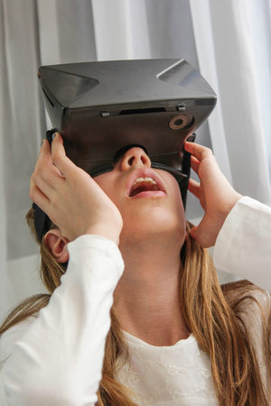futuristic girl: Girl in Virtual Reality headset looking up and trying to touch objects in virtual environment. Stock Photo