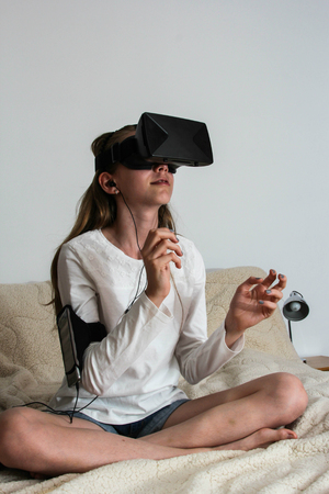 Girl in Virtual Reality headset and sound device looking up and trying to touch objects in virtual environment.