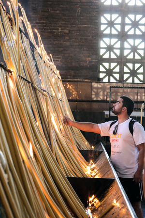 Aparecida, Brazil February 28, 2017: Unidentified pilgrim inside the chapel of candles at Basilica of the National Shrine of Our Lady Aparecida, considered the Patroness of Brazil.