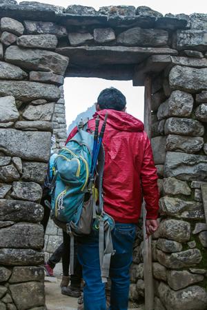 Machu Pichuu Pueblo, Peru - September 13, 2018: Unidentified tourist walking with backpack inside corridors of Machu Pichuu Cuzco, Peru. UNESCO World Heritage Site.