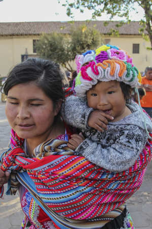 Machu Pichuu Pueblo, Peru - September 13, 2018: Unidentified woman with a baby in typical clothes on the street of Cuzco Peru
