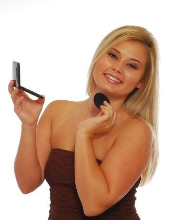 Smiling blond girl putting on makeup