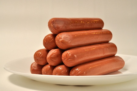 A pile of hot dogs on a white plate Stock Photo