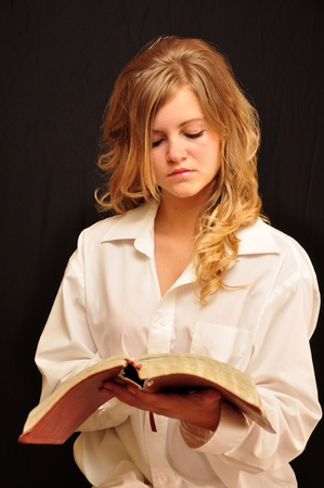 A attractive woman is reading her bible.
