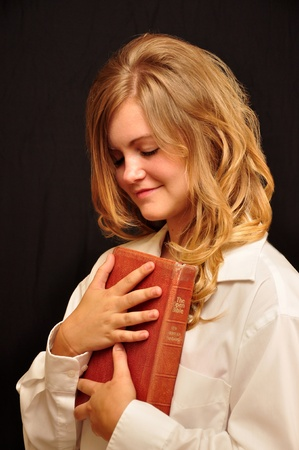 A pretty girl is holding a bible and praying, Stock Photo