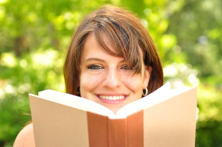 A young woman reading a book outdoors photo