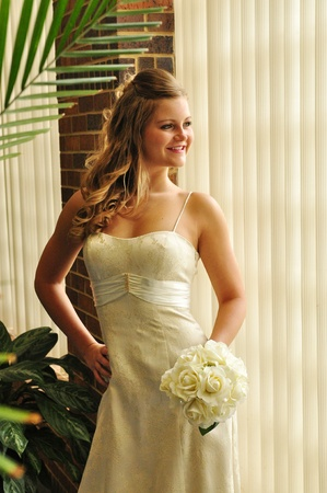 A young bride stands looking out of a window