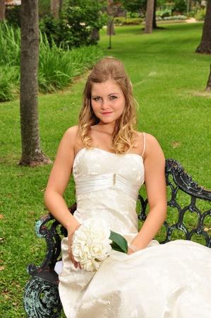 かわいい 20 代白人花嫁は公園のベンチに座って