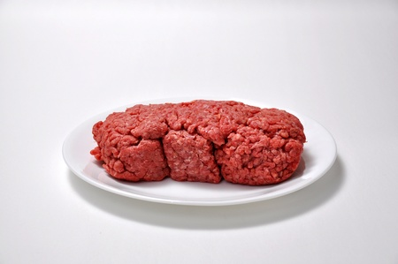 A pound of ground beef sits on a saucer on a white background