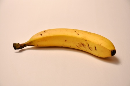 A lone banana lays on top of a white back ground.