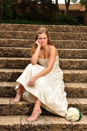 A young adult, 20s caucasian bride is sitting outside the church on stone steps after being left at the alter.