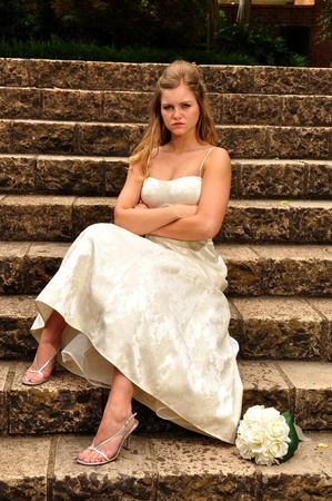 A mad caucasian 20 something young bride is waiting out side for her husband to bt to arrive .