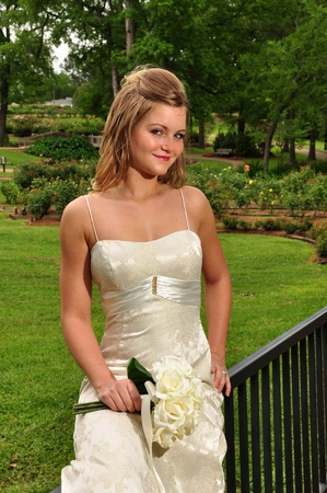 20 something: A 20 something  caucasian bride issitting out side holding her flowers. Stock Photo