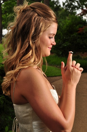 A young pretty Caucasian bride is out doors holding her husbands wedding band on her finger.